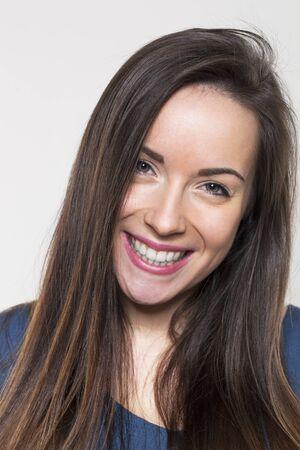 capelli lunghi: carino 20s sorridente ragazza bruna con i capelli lunghi esprimendo felicit� e giovent� marrone Archivio Fotografico