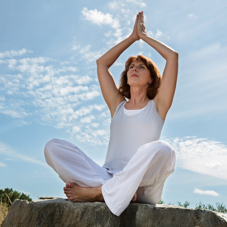 aging woman: senior zen - beautiful aging woman sitting on a stone in praying yoga position, wearing white, seeking serenity and balance in a park,summer daylight,blue sky,low angle view Stock Photo