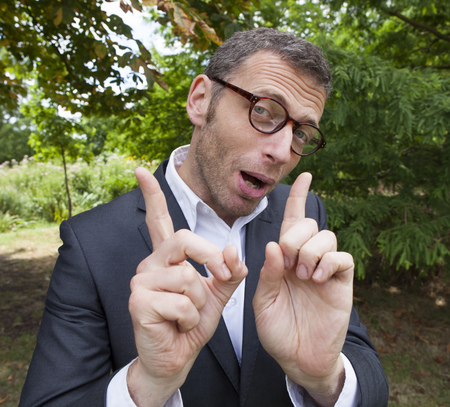 mad scientist outdoor concept - talkative businessman showing his hands in foreground talking in green environment for corporate involvement,natural summer daylight Foto de archivo