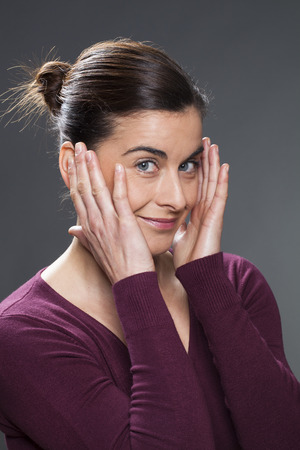 acupressure hands: cheerful 30s woman smiling in practising face acupressure with hands on face and temples for natural eye care and facial contour exercise