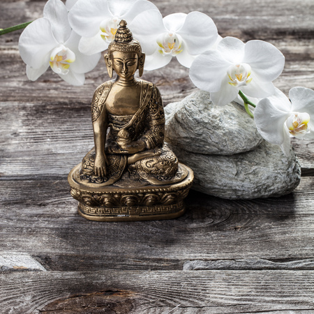 retreat: spa beauty treatment concept - symbol of spirituality for inner beauty with Buddha on old wood, gray texture stones and white orchid flower background for genuine retreat decor Stock Photo