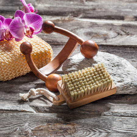 indulging: spa beauty treatment concept - symbols of massage, washing-up and nail care for indulging yourself set on old wood, gray texture stone and pink orchid flower background for genuine body care decor