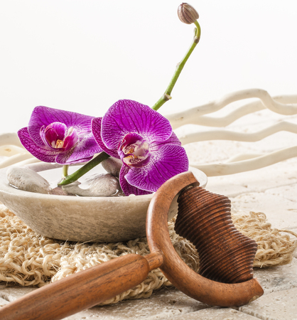 exfoliation: wellbeing still-life - massage and exfoliation setting with pink orchid flowers for purifying exfoliation at detox spa