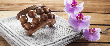 inner beauty: concept of massage and washing-up with towel, wooden accessory and orchid flowers for wellbeing