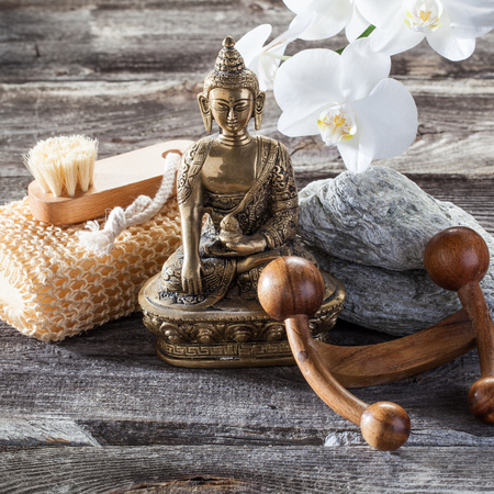 spa beauty treatment concept - cleansing, exfoliation and massage tools with spiritual symbol such as Buddha on old wood and gray stones background for genuine zen decor Stock Photo