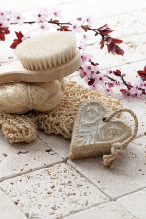 exfoliation: wellbeing still-life - back brush, loofah and heart-shape soap with cherry blossom flowers for soft exfoliation and hygiene at ayurveda spa Stock Photo