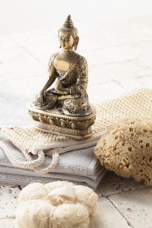 inner beauty: spirituality still-life - exfoliating massage and pampering set and bronze Buddha there is loofah towels and limestone