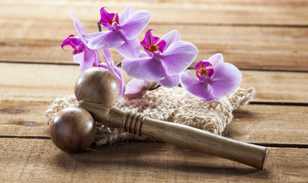 exfoliate: concept of massage and washing-up with loofah glove and orchids for exfoliation Stock Photo