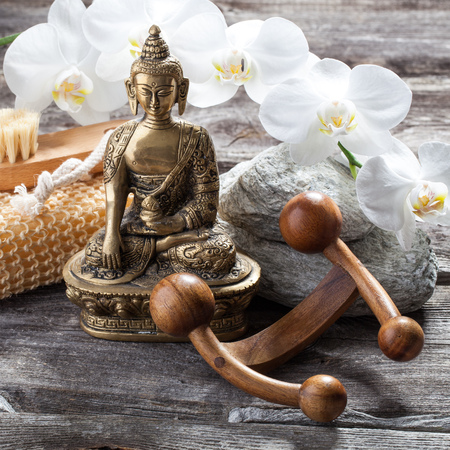 inner beauty: spa beauty treatment concept - symbol of massage and peeling for inner beauty with Buddha on old wood, gray texture stones and white orchid flower background for genuine feng shui decor