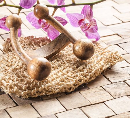 indulging: wellbeing still-life - pampering and indulging massage with exfoliation with loofah and wooden massager set on wood background with pink orchid flowers Stock Photo