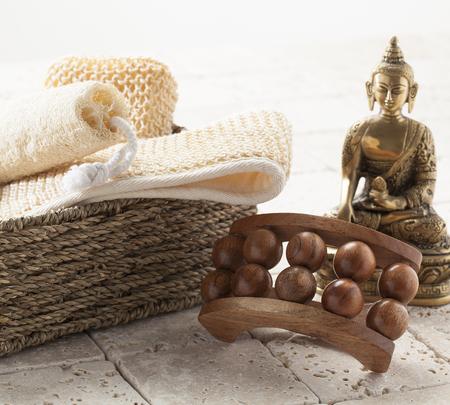 inner beauty: still-life wellbeing - exfoliating massage and pampering set on limestone with beautiful bronze Buddha