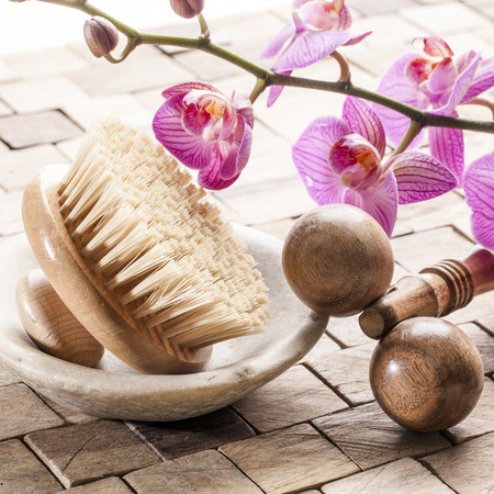 mimos: bienestar naturaleza muerta - mimos y disfrutando de masaje con exfoliaci�n corporal con el cepillo hacia atr�s y masajeador de madera situado en el fondo de madera con flores de color rosa orqu�dea Foto de archivo