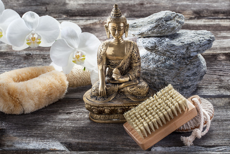 retreat: spa beauty treatment concept - symbol of cleansing and peeling for inner beauty with Buddha on old wood, gray texture stones and white orchid flower background for authentic retreat decor Stock Photo