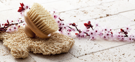 exfoliate: wellbeing still-life - back brush and loofah with cherry blossom flowers for soft exfoliation and body care at ayurveda spa