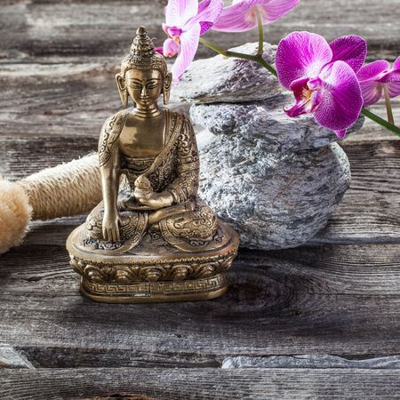 exfoliation: spa beauty treatment concept - symbol of exfoliation for inner beauty with Buddha on old wood, gray stones and pink orchid flower background for genuine zen ambiance Stock Photo