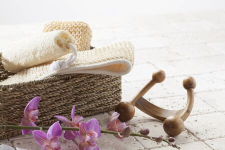 indulging: wellbeing still-life - exfoliating and indulging massage with wooden massager set on wood background with pink orchid flowers Stock Photo