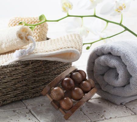 pampering: wellbeing still-life - exfoliating and pampering massage set on limestone with beautiful white orchid flowers for purity