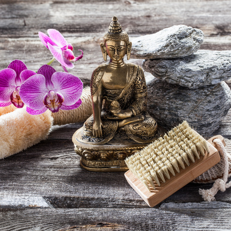 inner beauty: spa beauty treatment concept - symbol of detox and cleansing for inner beauty with Buddha on old wood, gray texture pebbles and pink orchid flower background for authentic zen decor Stock Photo