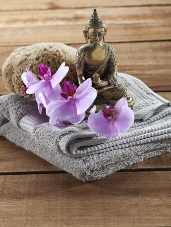 inner beauty: Buddha for spirituality at beauty spa with towel flower massage and ritual accessories Stock Photo