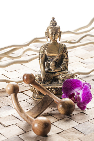 inner beauty: meditation still-life - meditating before ayurveda massage, Buddha on wood background with pink orchid flowers