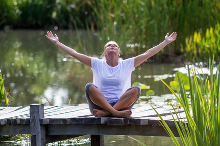 outstretching: outdoors relaxation - beautiful young yoga woman outstretching her arms,enjoying to relax on a wooden bridge with green foreground and water background, summer daylight
