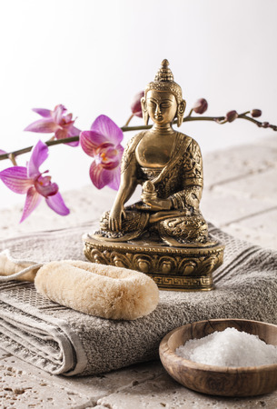 exfoliation: still-life wellbeing - energetic exfoliation setting with Buddha and bath salt for vitality and spirituality at detox spa