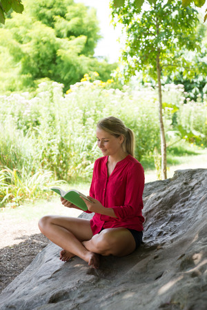 suntanned: outdoors reading - beautiful young suntanned blond woman reading on a giant stone in the shade for relaxation,natural summer daylight