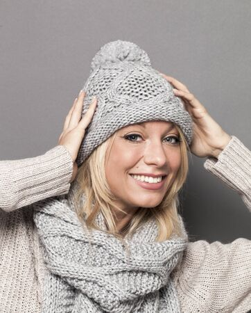 trendy warm winter - cute young blond woman wrapped up in gray wool winter hat and scarf smiling for comfort and cozy temperature