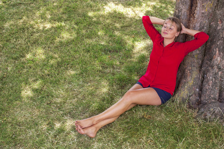 suntanned: wellbeing & tree concept - cheerful young suntanned blond woman lying under a tree,closing eyes enjoying freedom,natural summer daylight,view from above