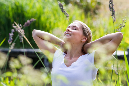 relaxed: relaxation outside - relaxed young woman daydreaming,enjoying sun and vacation with green surrounding, summer daylight