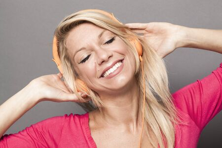 beat women: pretty young woman listening to fun music with headphones Stock Photo