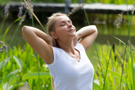 relaxation outdoors - happy young woman breathing,enjoying sun and vacation with green surrounding, summer daylight Foto de archivo