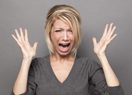 enojo: 20s frustrados niña rubia llorar, perdiendo los estribos, gritando en voz alta con las manos arriba