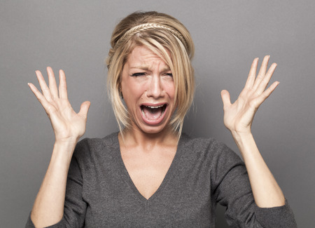 stressed woman: frustrated 20s blond girl crying, losing temper, screaming loud with hands up Stock Photo