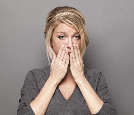 decepci�n: concepto de la tristeza - retrato de 20 a�os de moda mujer rubia con su�ter gris expresando su decepci�n y tristeza, tiro del estudio Foto de archivo