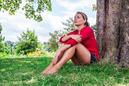 suntanned: reflection & tree concept - beautiful young blond suntanned woman resting in the grass in the shade for relaxation,natural summer daylight,low wide angle view Stock Photo