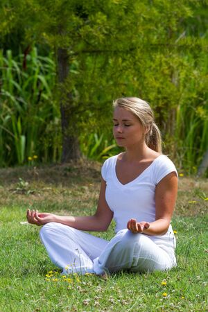 inner peace: outdoors meditation - focused young yoga woman exercising in lotus pose,closing eyes to focus on inner peace to relax and meditate on grass with green bushy background Stock Photo