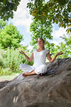 closing eyes: outdoors zen exercise - focused young yoga woman escaping in closing eyes,relaxing in lotus pose on a big stone, summer daylight