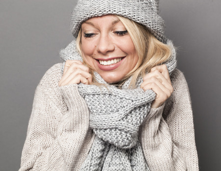 trendy warm winter - gorgeous young blond woman wrapping up herself in gray wool winter hat and scarf smiling for softness and cozy fashion Archivio Fotografico