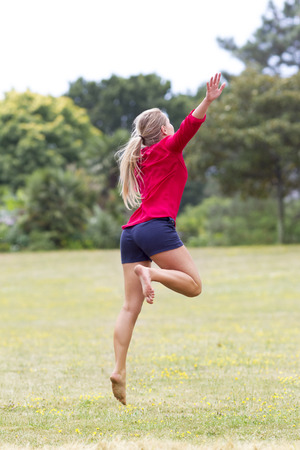 suntanned: celebrating success outdoors concept - dynamic beautiful young woman in shorts jumping with arms raised for fun and happiness in city park,natural summer daylight,view from the back