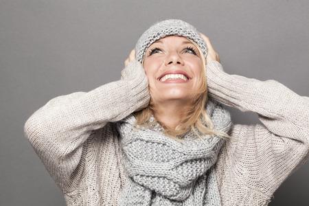 見上げる冬の帽子を身に着けているブロンドの髪と服、素敵な若い女性の手の楽しみと幸福のための耳 写真素材