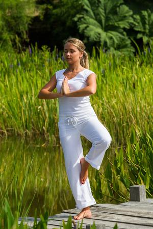 paz interior: al aire libre de la meditación - mujer hermosa joven que ejercita yoga equilibrio, cerrando los ojos para concentrarse en la paz interior para relajarse y meditar con el fondo verde y el agua, la luz del día verano Foto de archivo