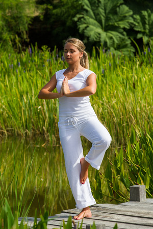 inner peace: outdoors meditation - beautiful young yoga woman exercising her balance,closing eyes to focus on inner peace to relax and meditate with green and water background, summer daylight Stock Photo