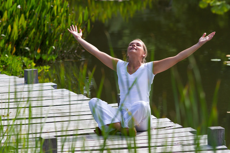 inner peace: outdoors meditation - relaxed young yoga woman enjoying outstretching arms,closing eyes to relax and meditate on a wooden bridge with green foreground and water background, summer daylight