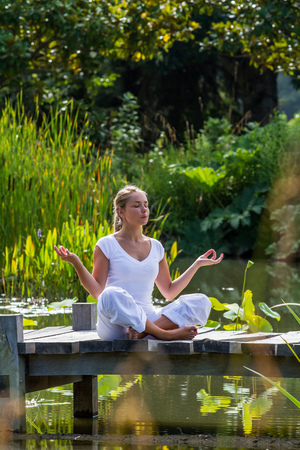 outdoors meditation - focused young yoga woman in lotus pose,breathing and meditating on a wooden path with green foreground and water lily background, summer exotic daylight