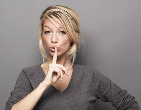 requiring: fun secret concept - cute 20s blond woman requiring silence and discretion with a finger on her lips,studio shot