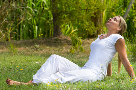 closing eyes: relaxation outdoors - happy young woman enjoying sun and vacation resting on grass, closing eyes with green surrounding, profile view, summer daylight