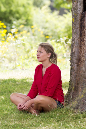 bare girl: reflection & tree concept - beautiful young blond woman sitting on the grass in the shade for relaxation,natural summer daylight Stock Photo