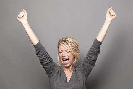 succes concept - lachende jonge blonde vrouw het winnen van een wedstrijd met leuke sexy lichaamstaal