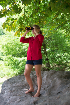 suntanned: environment observation concept - suntanned young blond woman standing high up on giant rock with binoculars to observe nature under tree in summer Stock Photo